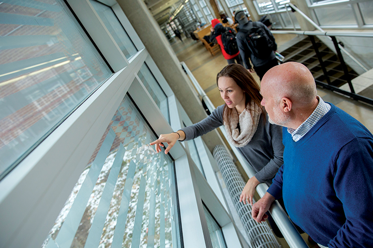Erica Gerloski and Glen Fredlund look at modifications made to windows prone to bird strikes at the School of Architecture & Urban Planning building.