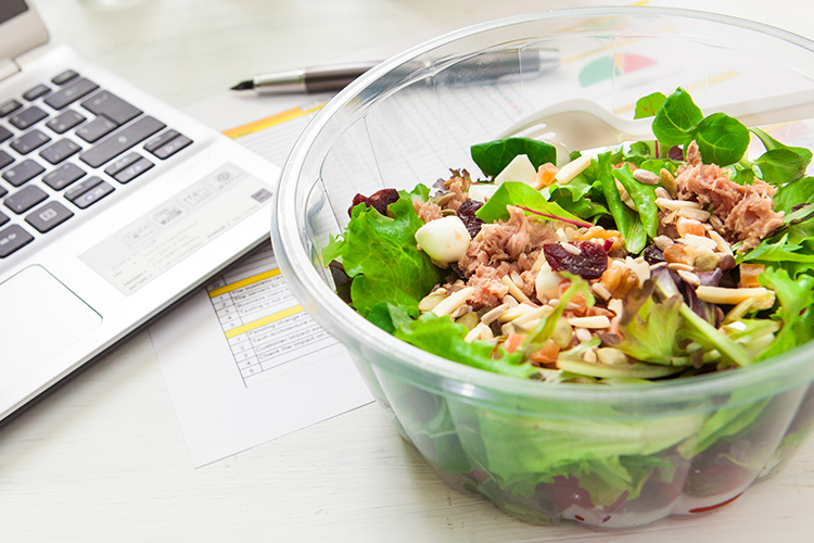 Bowl of salad next to a laptop