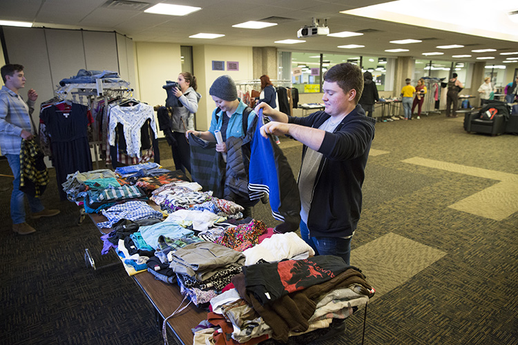 Two people look at clothes on a table.