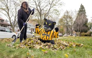 Pounce the UWM mascot mugs for the camera as a student rakes.