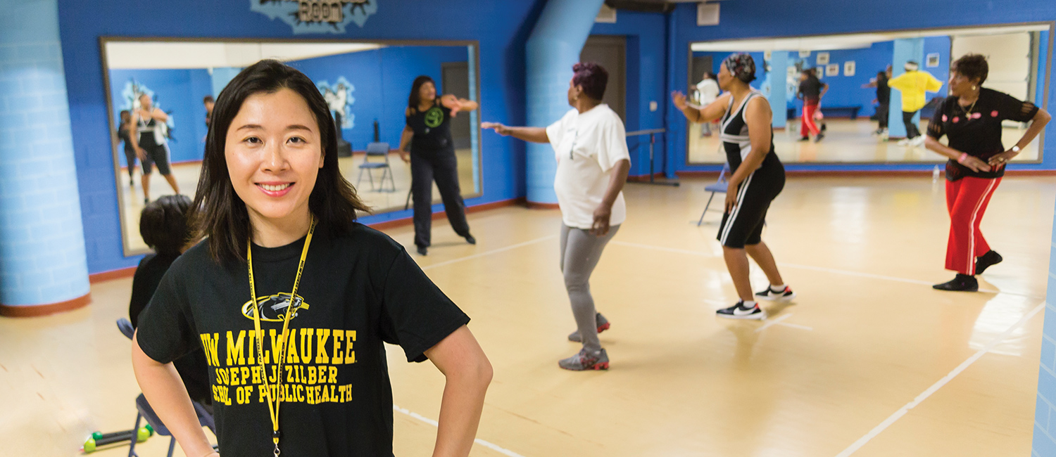 Alice Yan standing in a workout room as women exercise in the background