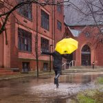 A student runs through the rain with a UWM umbrella.