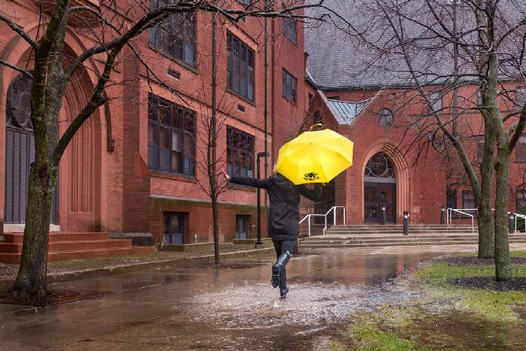A student runs through the rain with a UWM umbrella.