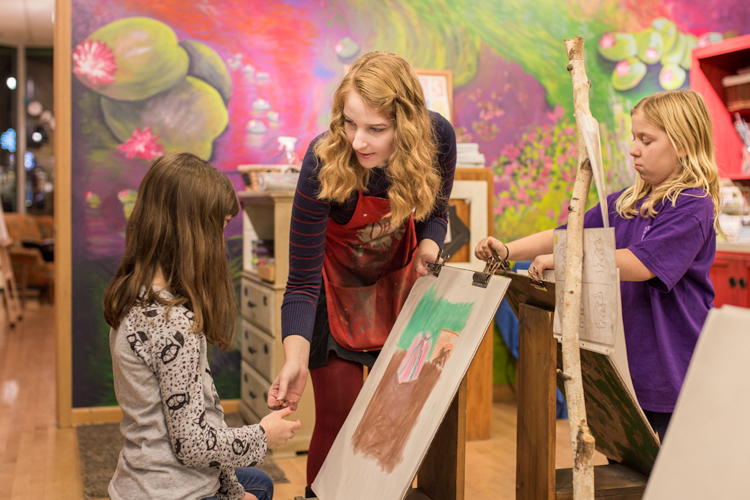 Melissa Hillmer helps a student with her painting.