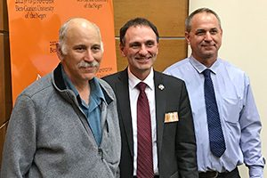 Three men pose for a photo.