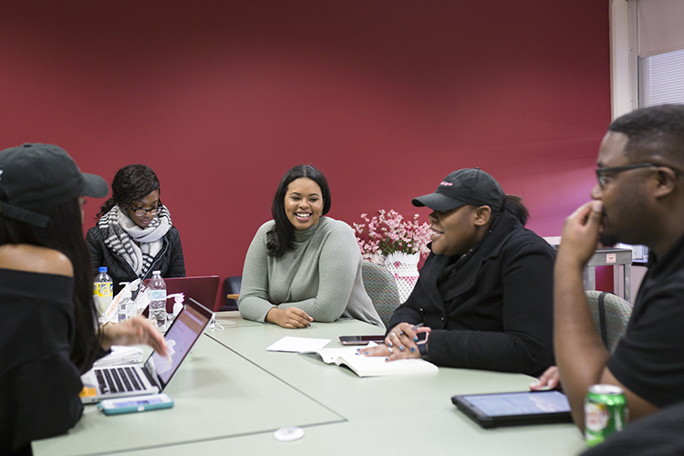 Several students sit around a table talking.