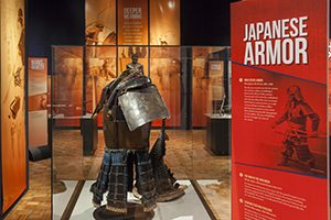 A suit of armor is displayed in a glass case.
