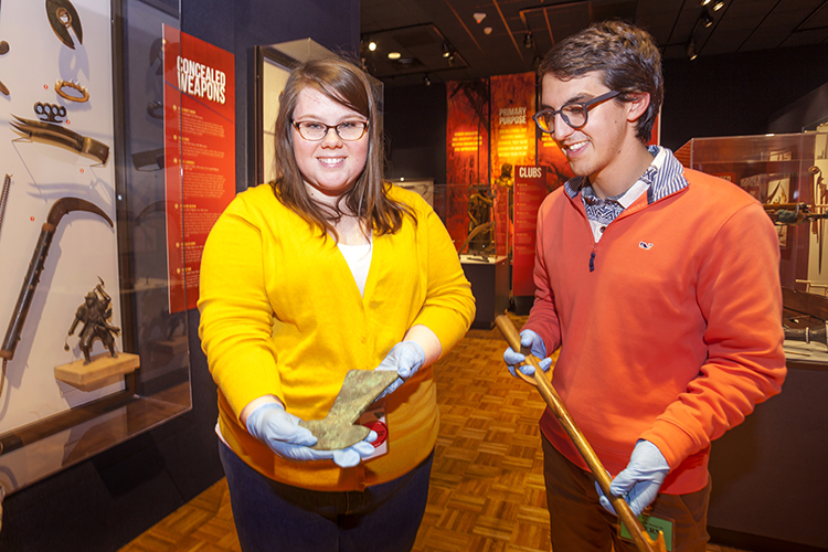 Two students show two antique weapons.