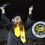 A student raises her arms in celebration.