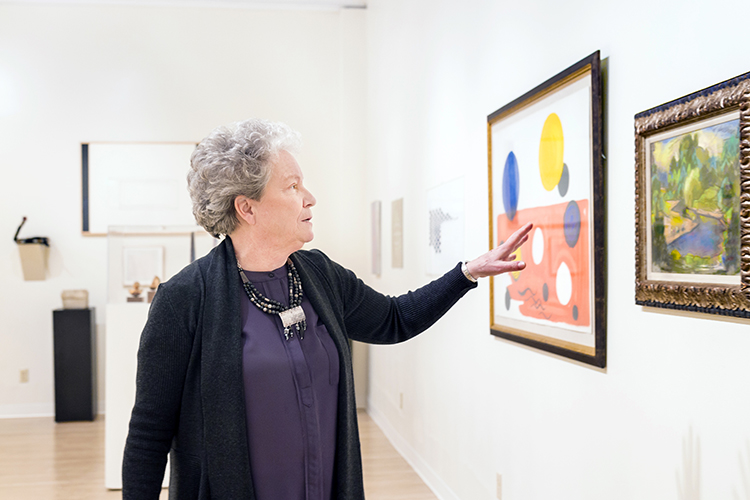 A woman gestures toward a drawing on the wall of a gallery.