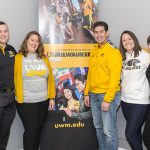 Five people stand and pose for a photo in front of a UWM poster.