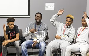 Several students raise their hands during a discussion.