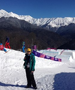Barbara Meyer stands on a ski hill with jumps.