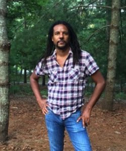 Colson Whitehead stands in a forested area