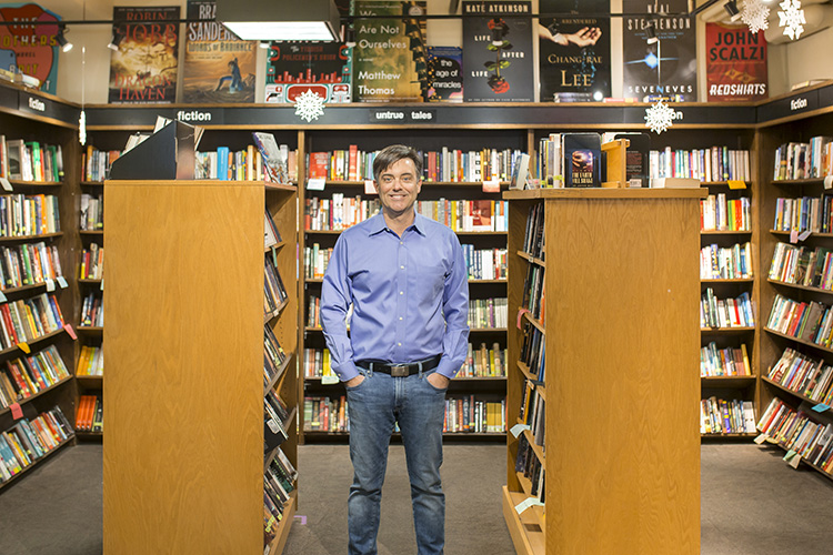 Liam Callanan stands between two racks of books at Boswell Book Company.