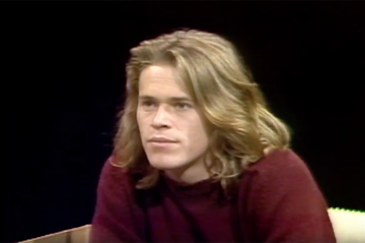 A young Willem Dafoe looks to the side.