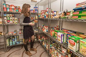 A student puts items on a shelf stocked with food.