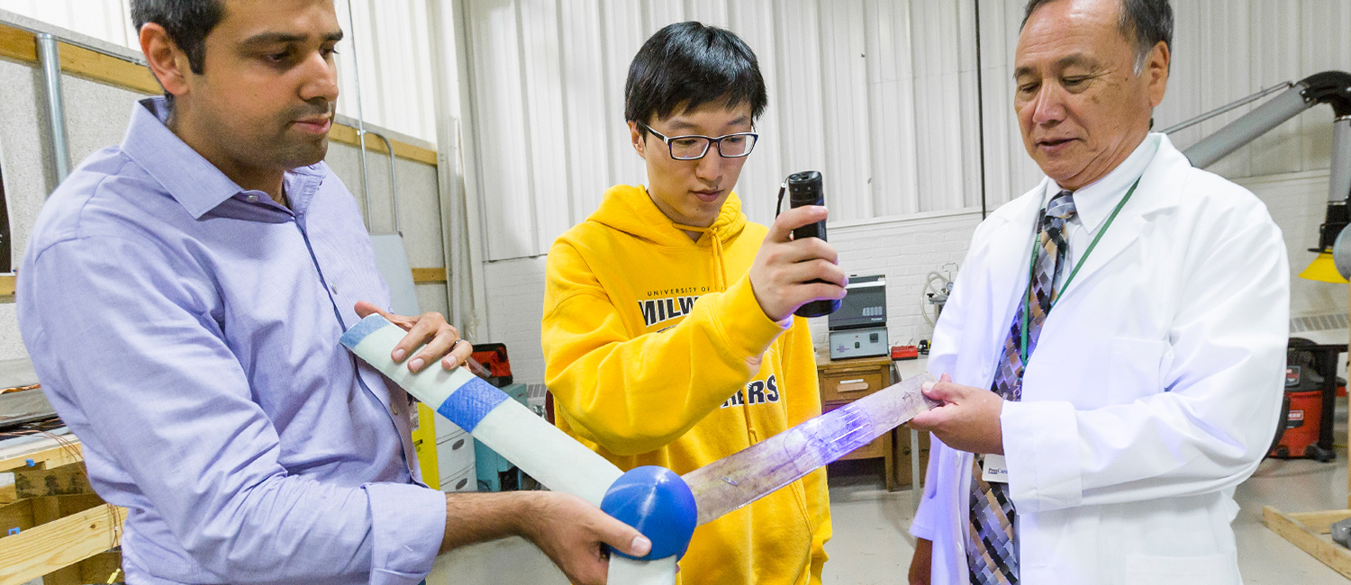 Postdoctoral researcher Saman Beyhaghi (left), undergraduate Jie Guo and Professor Ryoichi Amano use an ultraviolet light to display the hair-like glass tubes embedded in an experimental wind turbine blade.
