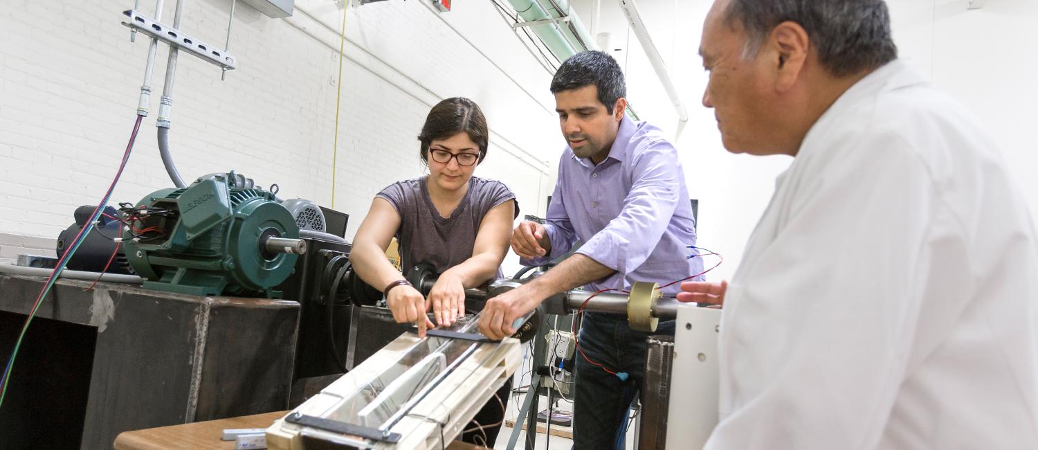 Beyhaghi helps Savavani adjust equipment in the gas turbine combustion lab while Amano looks on.