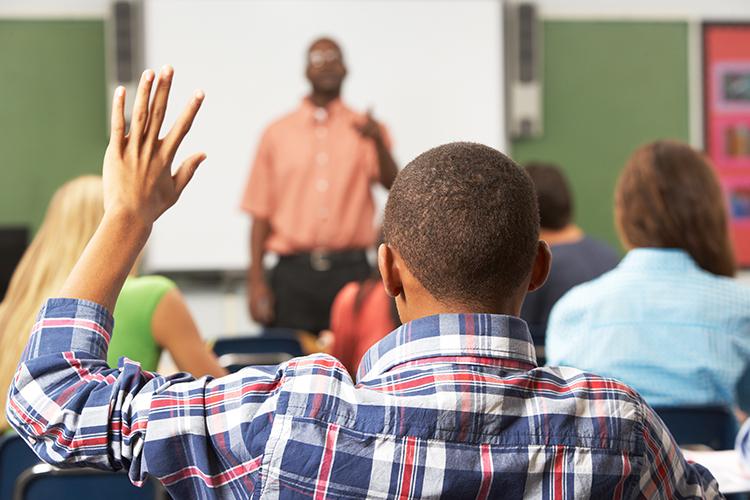Child raising his hand in class