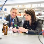 David Rice and Marcia Silva sit in a lab looking at a water sensor.