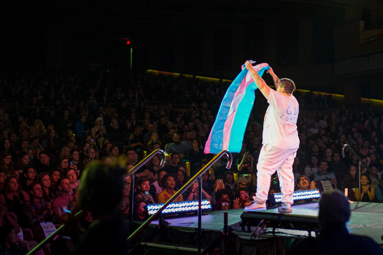 Travis Hard holding up a transgender pride flag for the audience.