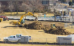 Two pieces of heavy equipment dig up a grass-covered section of ground.