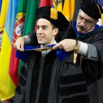Mohsen, wearing regalia, places a hood over a student in his graduation cap and gown