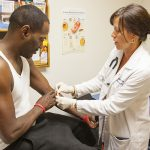 a nurse bandages a patient's arm after drawing blood