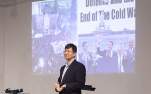 Uk Heo stands in front of a screen with an image of Ronald Reagan.