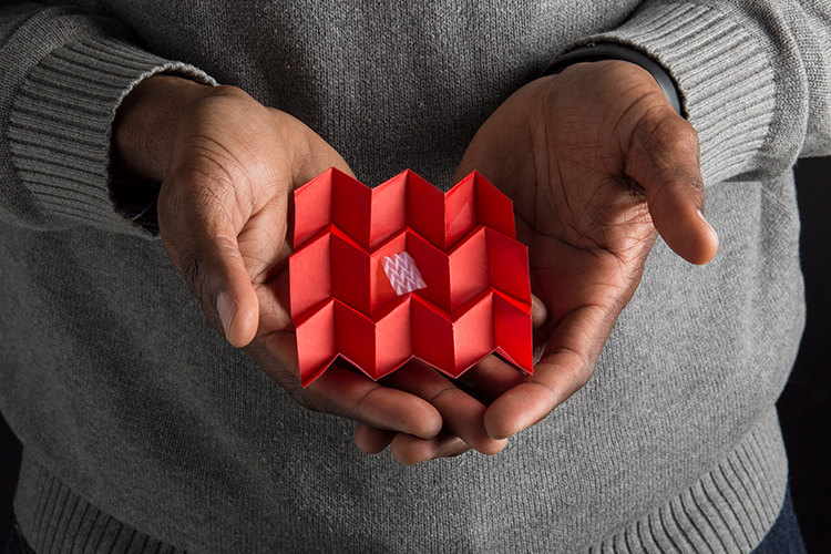 Close up of Jian Chen's hands holding small piece of foldable plastic and origami