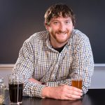 Grad student Josh Driscoll holds a glass of beer.