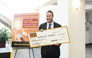 Jared Judge stands with an oversized check for $8,000.