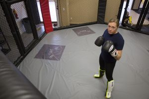 Leah Letson posing for a picture in a UFC-style fighting cage.