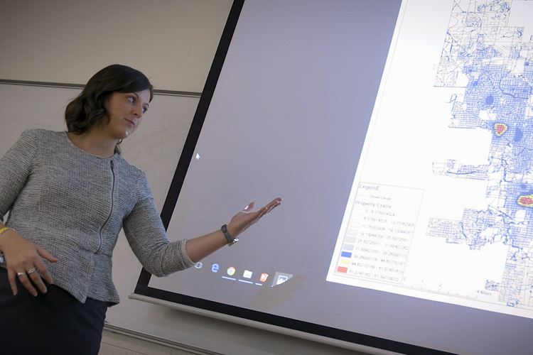 Stephanie Sikinger points to a whiteboard in a classroom