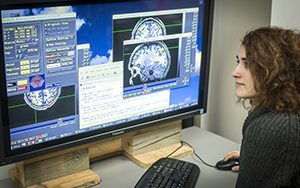 A woman looks at images of brains on a computer screen.