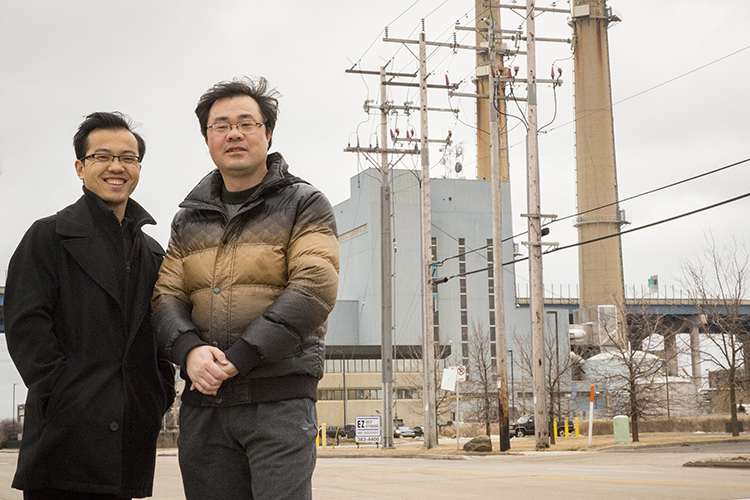 Wei Wei and Lingfeng Wang stand on a street in front of some power lines.