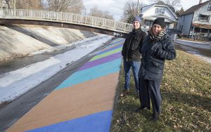 Two people stand along the edge of the concrete channel lining the Kinnickinnic River.