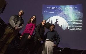 Four people stand in the planetarium in front of a projection of a title slide.