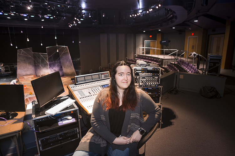 A student sits at a control panel with the theater in the background.