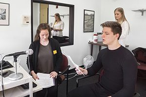 Two students watch and evaluate a voice student as he sings into a microphone.