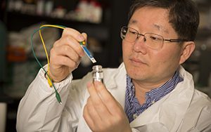 Woo-Jin Chang is puts a water sensor into a sample of water.