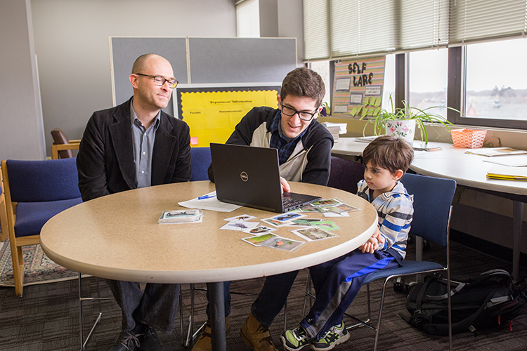 A man and a grad student sit at a table with a child.