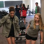 Two girls carry an exercise bike out of a brightly lit room
