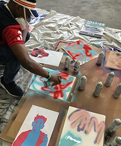 A man crouches as he creates art with spray paint.