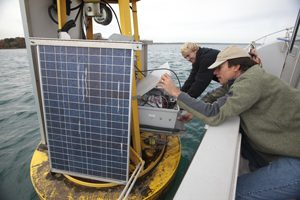 Two men examine research equipment on a boat on Lake Michigan.