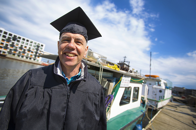 A man stands in a graduation gown and cap in front of a boat.