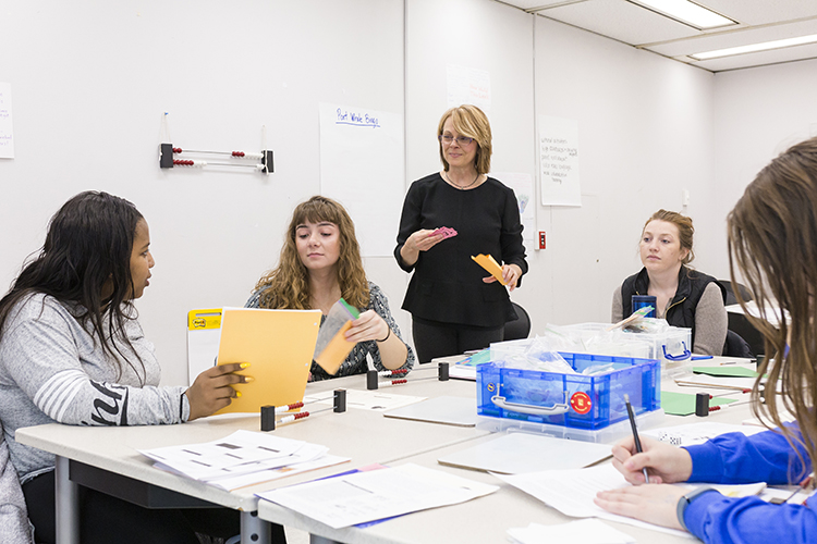 A woman stands while teaching several students.