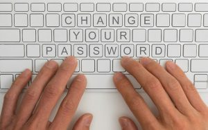 """Two hands on top of a computer keyboard with the words """"Change Your Password"""" spelled out on the keys."""