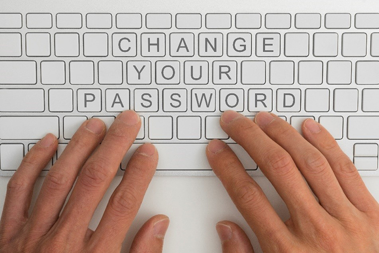 "Two hands on top of a computer keyboard with the words ""Change Your Password"" spelled out on the keys."